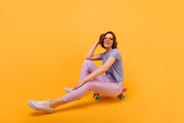 Ekstatisches mädchen in der rosa hose, die gute gefühle mit longboard ausdrückt. innenfoto des attraktiven weiblichen modells, das auf skateboard aufwirft.