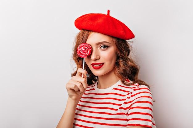 Ekstatisches rothaariges mädchen, das mit süßigkeit steht. innenporträt der eleganten französischen frau mit lutscher.