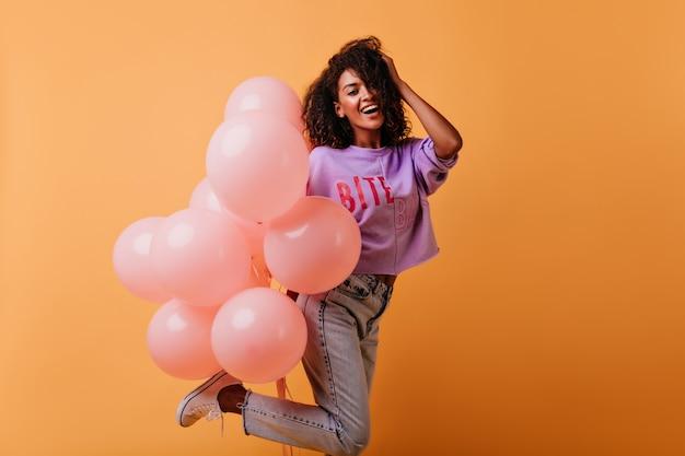 Ekstatisches weibliches modell in jeans, die an der geburtstagsfeier tanzen. afrikanisches debonair-mädchen, das bündel von heliumballons hoding.