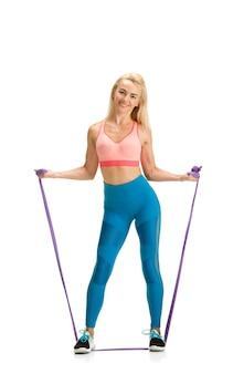 Elastisches band. schöner weiblicher fitnesstrainer, der auf weißer studiowand übt und übungen zeigt