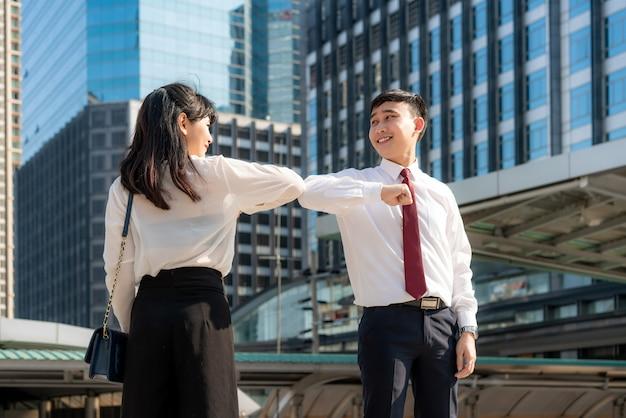 Elbow bump ist eine neue neuartige begrüßung, um die ausbreitung des coronavirus zu vermeiden. zwei asiatische geschäftsfreunde treffen sich vor dem bürogebäude. anstatt mit einer umarmung oder einem händedruck zu grüßen, stoßen sie stattdessen an die ellbogen.