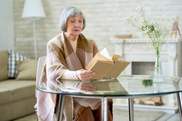 Elegante ältere dame, die ein buch liest