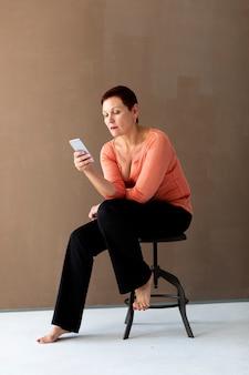 Elegante ältere frau, die ihr telefon überprüft