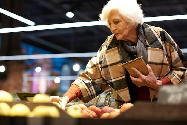 Elegante ältere frau im lebensmittelgeschäft