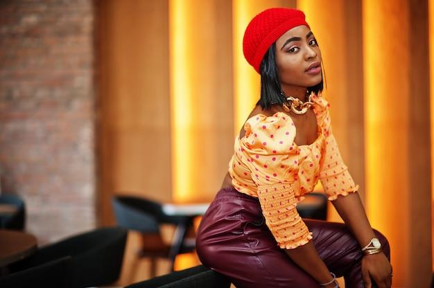 Elegante afro-amerikanerin in roter französischer baskenmütze, gepunkteter bluse mit großer goldener halskette und lederhose posieren im innenbereich.