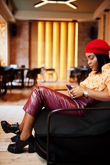 Elegante afro-amerikanerin in roter französischer baskenmütze, großer goldener halskette polka dot bluse und lederhose sitzen auf hocker mit handy.