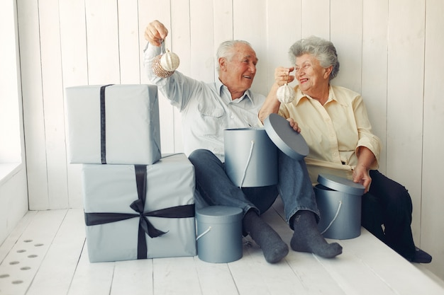 Elegante alte paare, die zu hause mit weihnachtsgeschenken sitzen