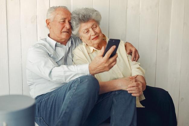Elegante alte paare, die zu hause sitzen und ein telefon verwenden