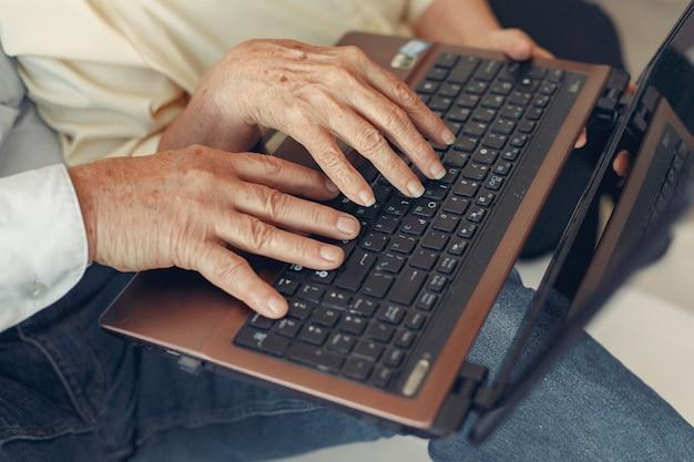 Elegante alte paare, die zu hause sitzen und einen laptop verwenden