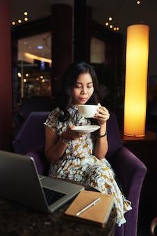 Elegante asiatin, die cappuccino im café und laptop liegen auf tabelle genießt
