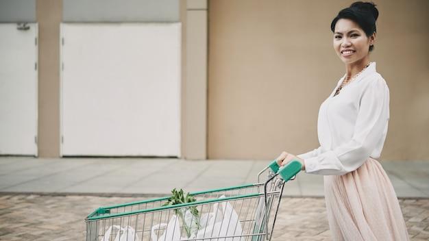 Elegante asiatin, die warenkorb mit taschen durch parkplatz drückt