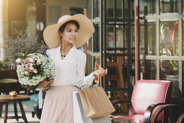 Elegante asiatische dame, die aus café mit einkaufstaschen und blumenblumenstrauß heraus geht