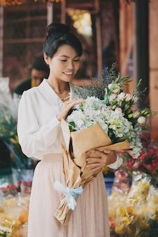 Elegante asiatische dame, die durchdachten blumenstrauß der frischen blume am blumengeschäft bewundert