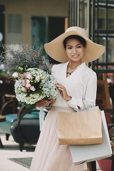 Elegante asiatische dame im großen strohhut, der mit einkaufstaschen und blumenblumenstrauß aufwirft