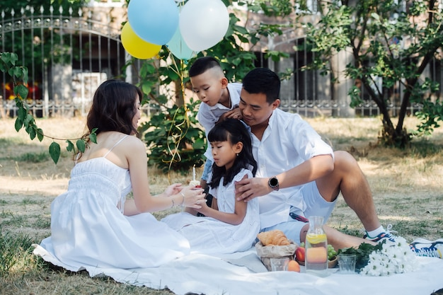 Elegante asiatische familie, die den geburtstag ihres kleinen mädchens in einem park mit einem kleinen kuchen feiert. eltern und ihre kinder in weißer kleidung in einem baumschatten.