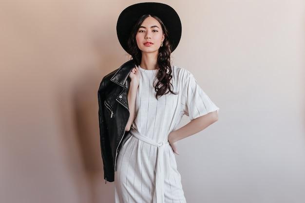 Elegante asiatische frau im weißen kleid, das kamera betrachtet. zuversichtlich chinesische frau im hut, der lederjacke hält.