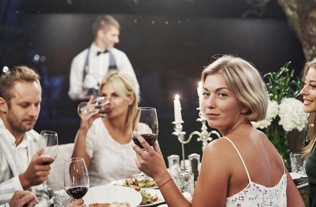 Elegante atmosphäre. eine gruppe erwachsener freunde ruht sich abends im hinterhof des restaurants aus und unterhält sich.