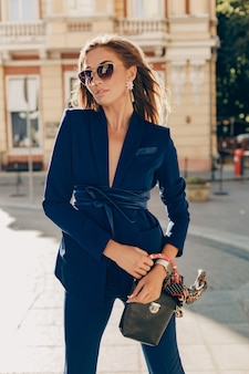Elegante attraktive frau, die blauen stilvollen anzug und sonnenbrille trägt, die in der straße hält, die handtasche hält