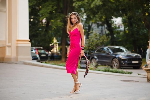 Elegante attraktive frau, die rosa sexy sommerkleid trägt, das in der straße hält handtasche hält