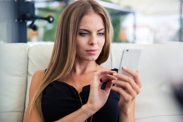 Elegante attraktive frau, die smartphone im restaurant verwendet