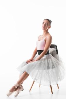 Elegante ballerina, die auf dem träumenden stuhl sitzt