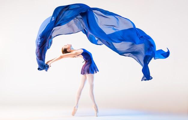Elegante ballerina in den punkten tanzt mit einem sich entwickelnden blauen tuch auf einem weißen hintergrund