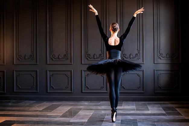 Elegante ballerina in einem schwarzen tutu und spitzenschuhen, die auf einer dunkelgrauen wand tanzen