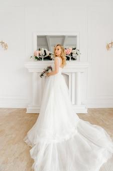Elegante blonde braut im schönen hochzeitskleid, das im innenstudio aufwirft.