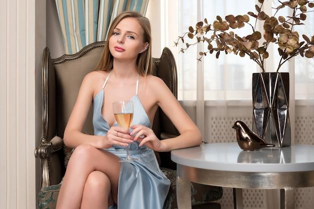 Elegante blonde dame mit glas wein im restaurant. schöne sexy junge frau mit langem haar perfektem körper und hübschem gesichts-make-up, das blaues abendkleid trinkend alkohol im luxusinnenraum trägt.