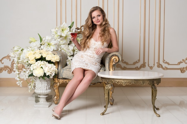 Elegante blonde dame mit glas wein im restaurant. schöne sexy junge frau mit langem haar perfektem körper und hübschem gesichts-make-up, das blaues kleid trägt, das alkohol im hellen luxus-interieur trinkt