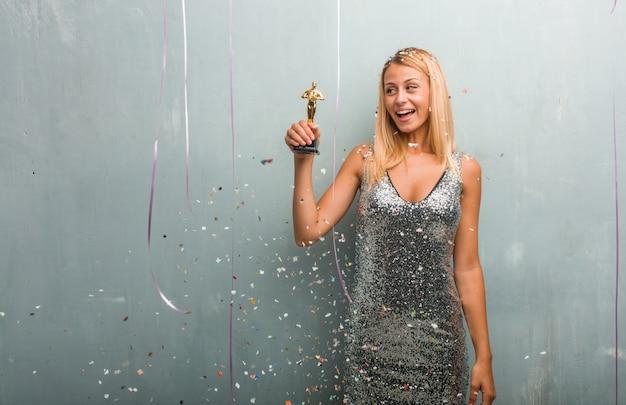 Elegante blonde frau, die einen preis, feier mit confetti empfängt.