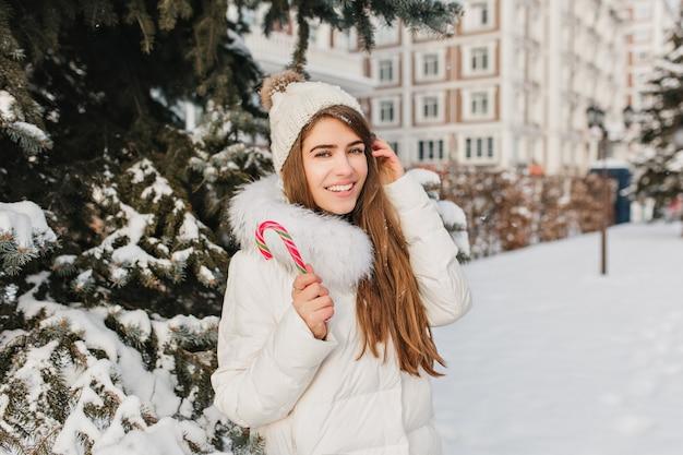 Elegante blonde frau, die mit glücklichem lächeln posiert, das süße zuckerstange am wintertag isst. porträt der herrlichen europäischen frau in der strickmütze, die neben der schneebedeckten fichte steht und lacht.