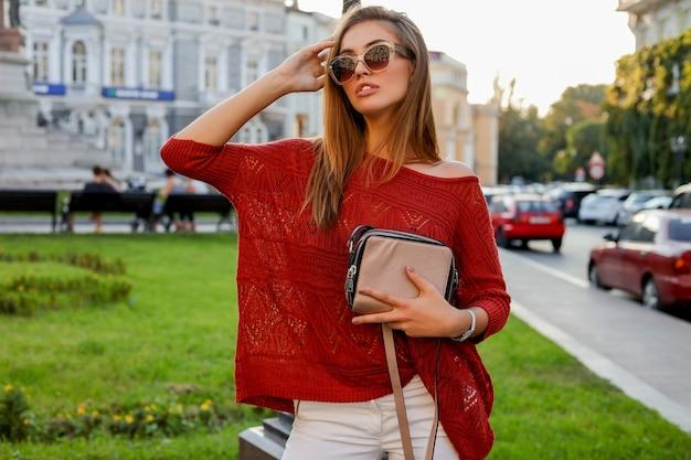 Elegante blonde frau im trendigen herbst ourfit posiert auf der straße. tragen von sonnenbrille, pullover und weißer jeans.