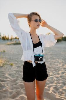 Elegante blonde frau mit retro-kamera, die grimassen macht und auf dem strand nahe ozean aufwirft. sommerferien. schönes sonnenlicht.
