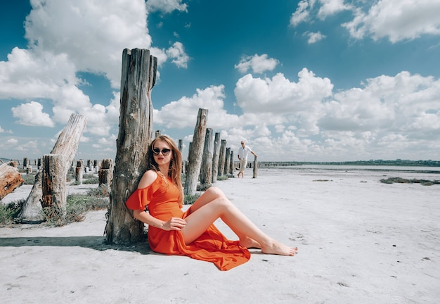 Elegante blonde frau mit rotem kleid am strand