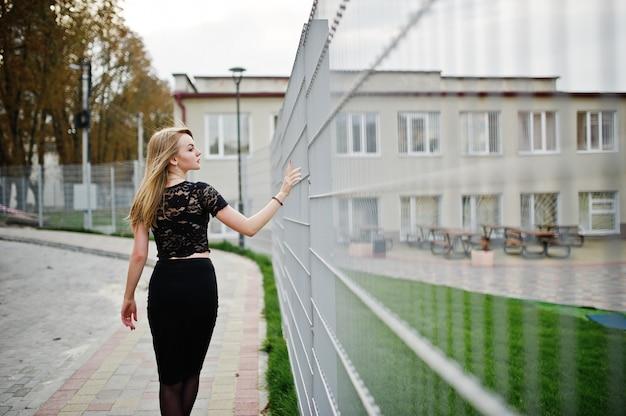 Elegante blonde mädchenabnutzung auf dem schwarzen, das an den straßen der stadt gegen eisenkäfig aufwirft.