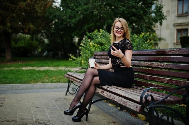 Elegante blonde mädchenabnutzung auf dem schwarzen, das an den straßen der stadt, sitzend auf bank mit tasse kaffee und handy an den händen aufwirft.