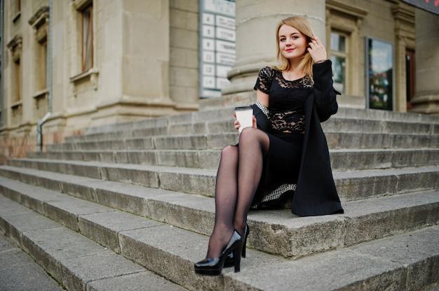 Elegante blonde mädchenabnutzung auf dem schwarzen, das an den straßen der stadt, sitzend auf treppe mit tasse kaffee an den händen aufwirft.