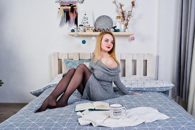 Elegante blonde mädchenabnutzung auf dem warmen kittel, der auf bett sitzt und las buch mit schale heißem kaffee.