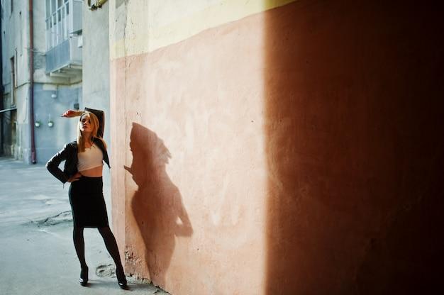 Elegante blonde mädchenabnutzung auf der schwarzen lederjacke, die an den straßen der stadt, alte wand mit schatten aufwirft.