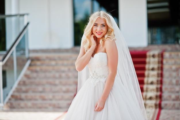 Elegante blonde modebraut der blauen augen an der großen hochzeitshalle auf rotem teppich