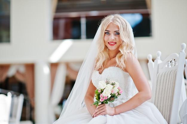 Elegante blonde modebraut der blauen augen an der großen hochzeitshalle, die auf stuhl sitzt