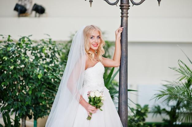 Elegante blonde modebraut der blauen augen an der großen hochzeitshalle