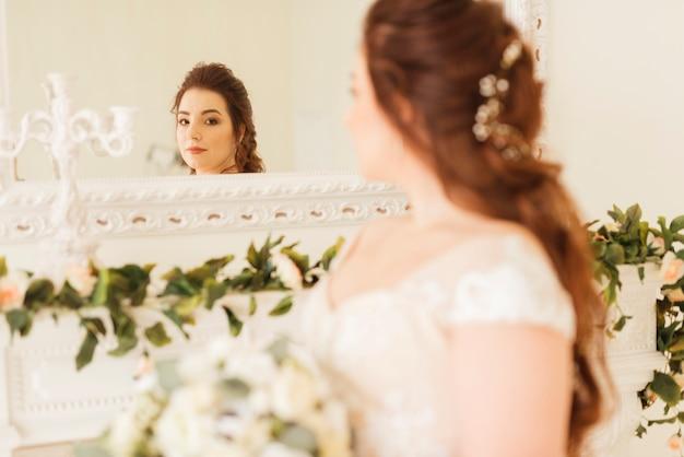 Elegante braut, die ihre reflexion betrachtet