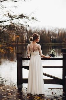 Elegante braut im weißen hochzeitskleid mit blumenstrauß durch see