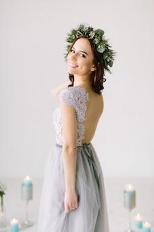 Elegante braut in einem pastellkleid posiert im studio vor der hochzeitszeremonie