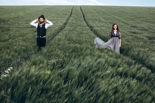 Elegante braut und bräutigam, die auf grünem feld gehen und aufwerfen