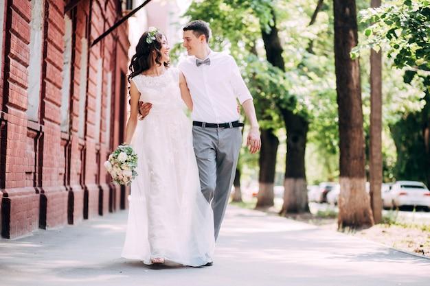 Elegante braut und bräutigam, die zusammen draußen an einem hochzeitstag aufwerfen