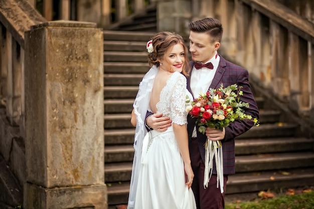 Elegante braut und bräutigam, die zusammen draußen an einem hochzeitstag aufwirft