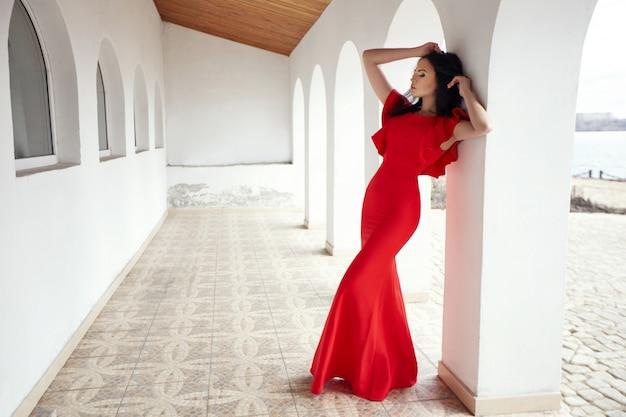 Elegante brünette frau im roten kleid steht nahe den wänden der alten villen am meer.